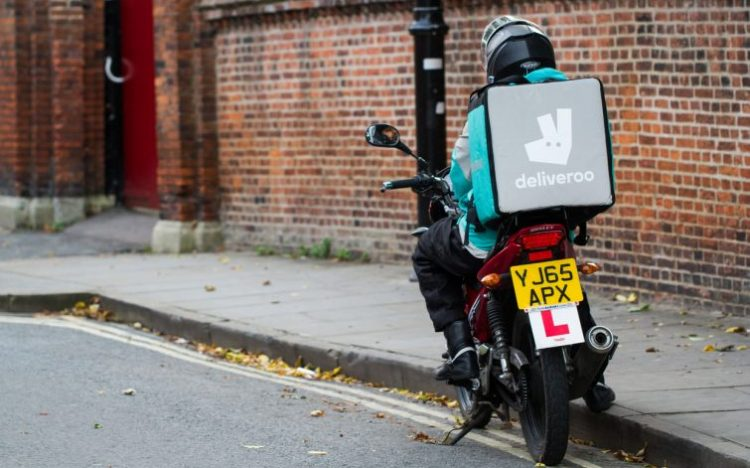 YORK, UK - SEPTEMBER 28' 2016. A motorcycle delivery driver from the increasingly popular take away food delivery company Deliveroo, waiting at the side of the road for his next order.
